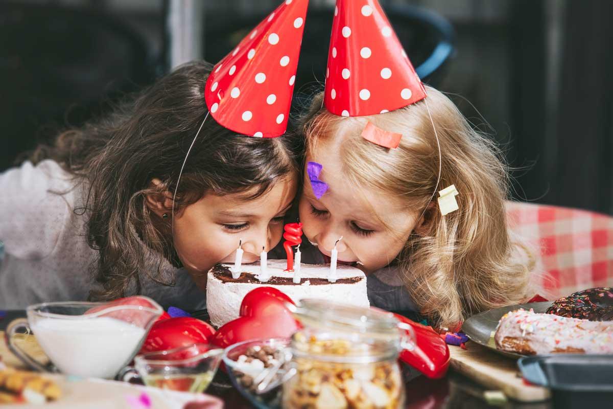 zwei Mädchen mit lustigen Hüten nachen von einer Geburtstagstorte