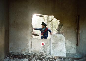Ein Junge im Bahnwärterkostüm klttert von außen durch ein Loch in der Wand