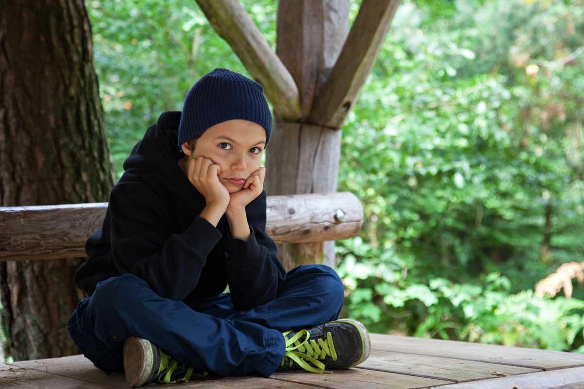 Junge sitzt gelangweilt auf einer Bank