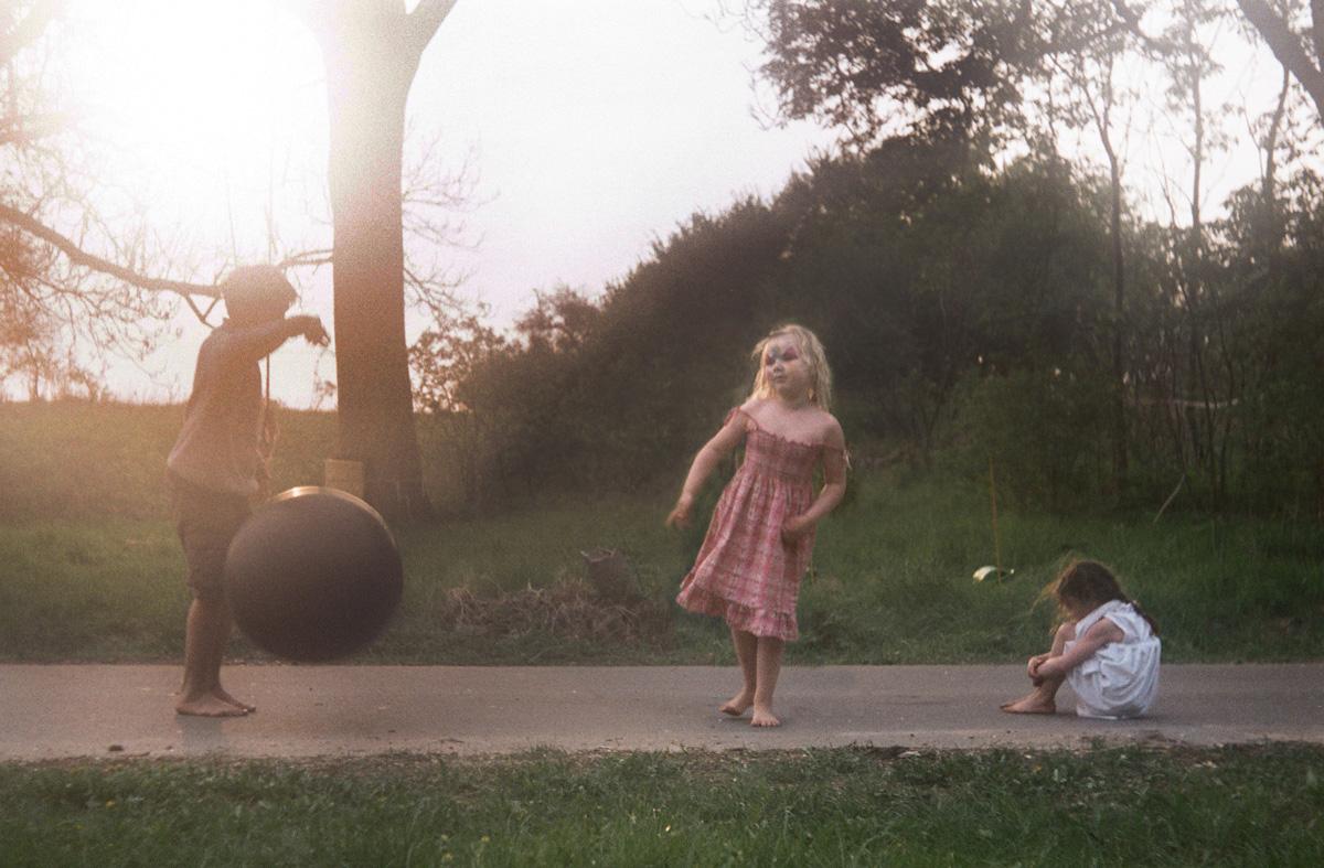 Drei Kinder auf der schmalen Dorfstraße im Spätsommerlicht mit schwarzem Ball und Gesichtsbemalung