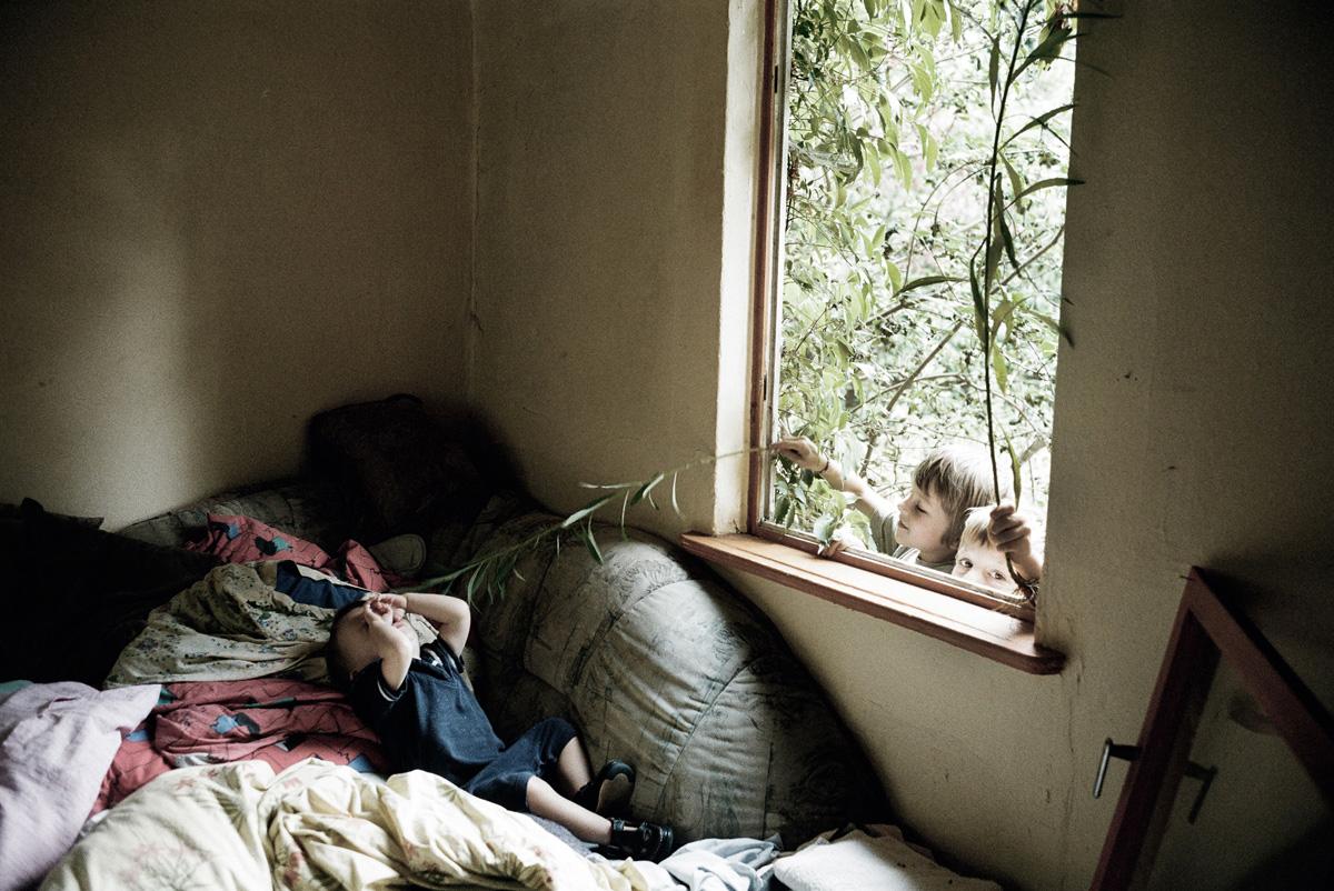Kinder am Fenster necken schlafends Kind im Zimmer