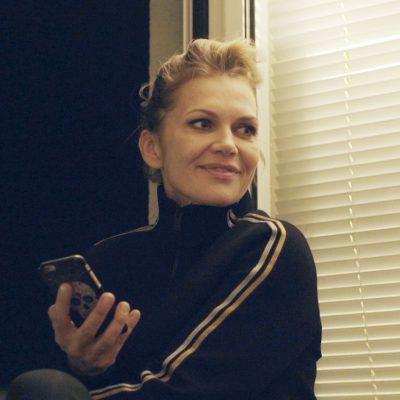 Anna Loos mit Handy frei von Angst auf dem Fensterbrett