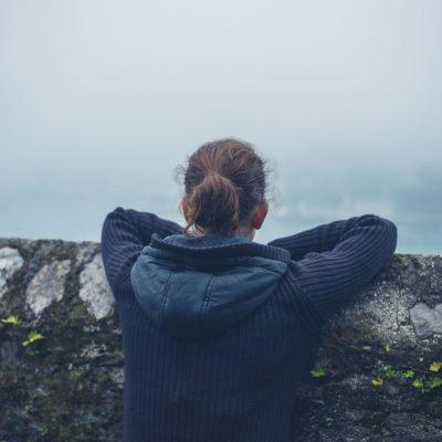 Verlassene Frau mit Blick in den Nebel