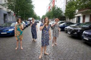 4 Männer barfuß auf der Kopfsteinpflasterstraße in petite fleur Kleidern essen Eis