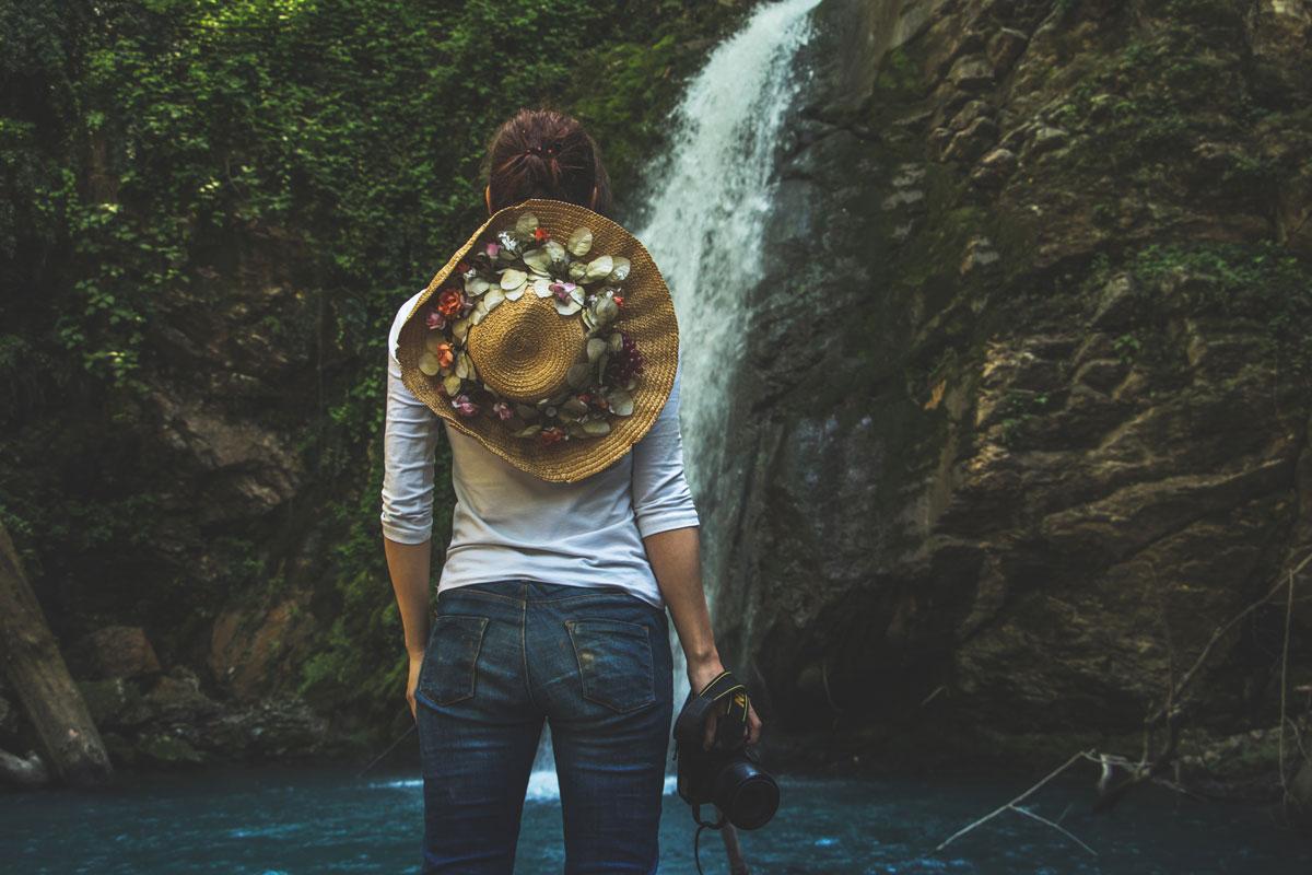 Frau mit Strohhut und Kamera vor einem Wasserfall