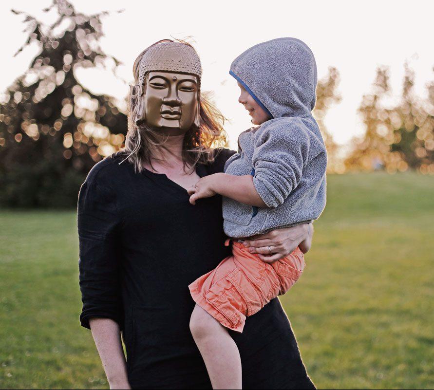 Frau mit Bhuddamaske und Kind im Arm