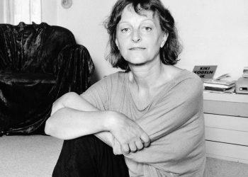 Die DDR Fotografin Helga Paris sitzend auf dem Teppichboden