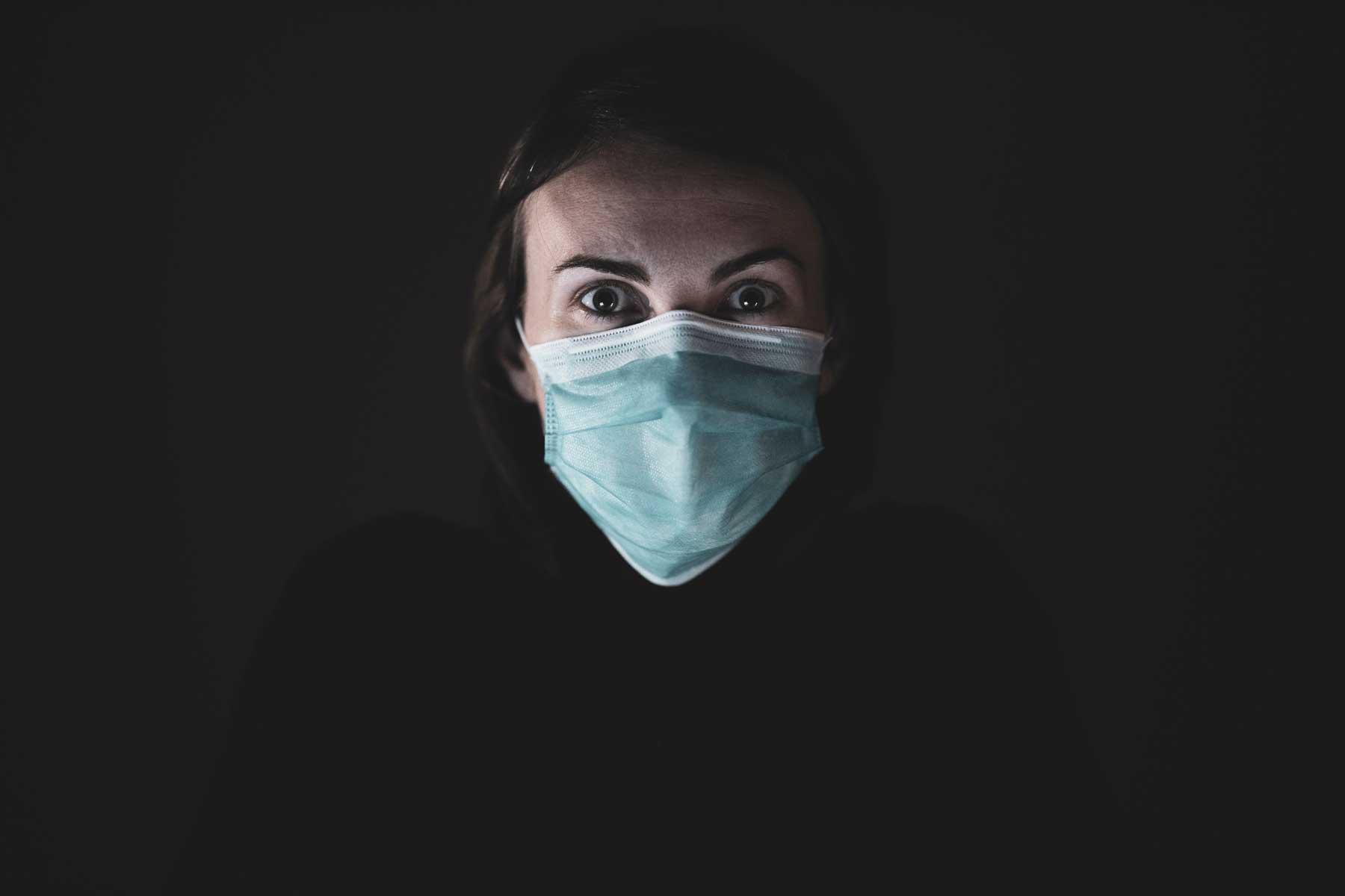 Erschrockene Frau mit medizinischem Mund-Nasenschutz