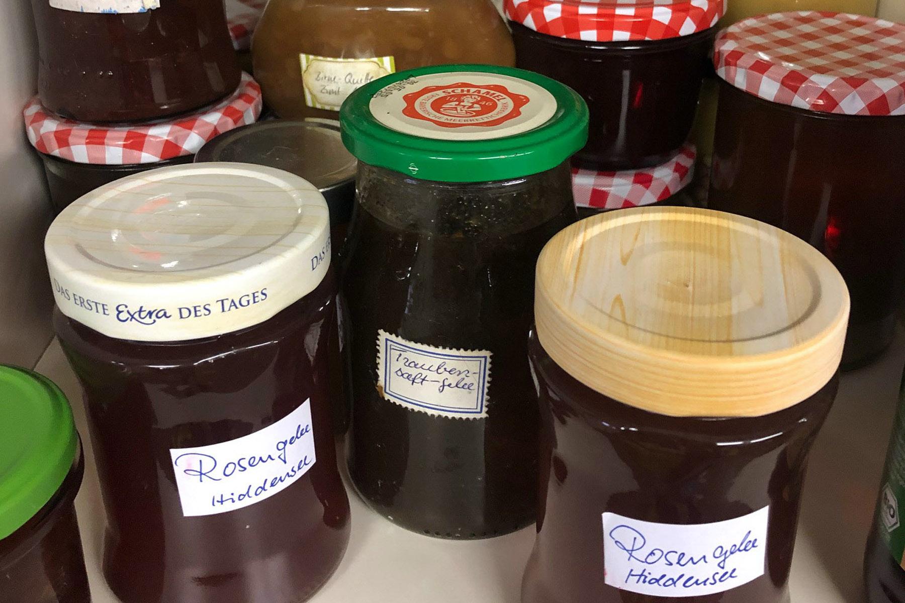 Mehrere Marmeladegläser in einem Lagerregal im Keller